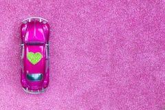 La voiture ultra-violette de jouet porte le coeur vert d'amour sur le toit Concept d'invitation de carte postale de mariage ou de Photos stock