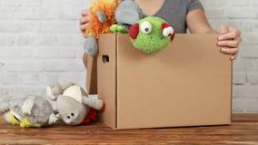 La volontaire de femme met de vieux jouets dans la boîte de donation images stock