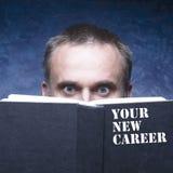 La vostra nuova carriera scritta sul libro nero Uomo maturo dietro il libro sopra Fotografia Stock Libera da Diritti