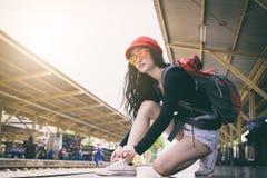 La voyageuse asiatique de femme a attacher des dentelles de chaussure pour voyager par chemin de fer photographie stock libre de droits