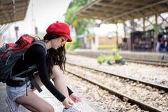 La voyageuse asiatique de femme a attacher des dentelles de chaussure pour voyager par chemin de fer images stock