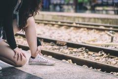 La voyageuse asiatique de femme a attacher des dentelles de chaussure pour voyager par chemin de fer image libre de droits