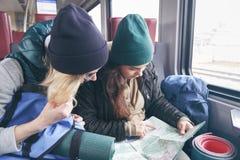 La voyageuse de deux amies avec des sacs à dos et l'inventaire entrent dans le train et observent l'itinéraire supplémentaire sur Photographie stock libre de droits