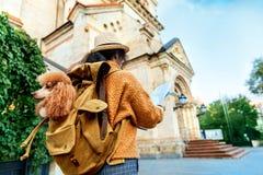 La voyageuse de femme avec le chien dans le sac à dos examine le monument architectural photos libres de droits