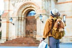 La voyageuse de femme avec le chien dans le sac à dos examine le monument architectural images stock