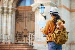 La voyageuse de femme avec le chien dans le sac à dos examine le monument architectural photo stock