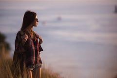 La voyageuse de femme regarde le bord de la falaise sur la baie de mer des montagnes à l'arrière-plan le coucher du soleil Photos libres de droits