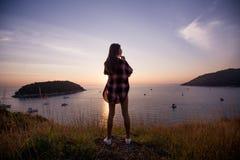 La voyageuse de femme regarde le bord de la falaise sur la baie de mer des montagnes à l'arrière-plan le coucher du soleil Photos stock