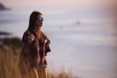 La voyageuse de femme regarde le bord de la falaise sur la baie de mer des montagnes à l'arrière-plan le coucher du soleil Images stock