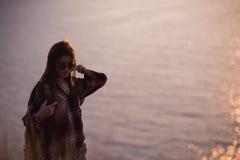 La voyageuse de femme regarde le bord de la falaise sur la baie de mer des montagnes à l'arrière-plan le coucher du soleil Images libres de droits