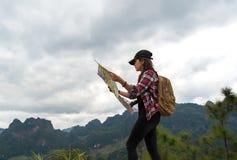 La voyageuse de femmes avec le sac à dos vérifie la carte Image stock