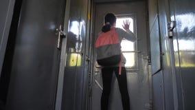 La voyageuse de fille d'adolescent avec le sac à dos se tient prêt la fenêtre de la voiture de train avec un smartphone Transport clips vidéos