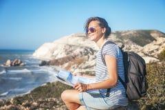 La voyageuse de jeune femme de fille avec un sac à dos et une carte marche à disposition photographie stock libre de droits