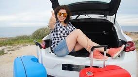 La voyageuse heureuse de femme avec des valises s'approchent de sa voiture banque de vidéos