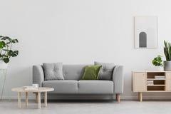 La vraie photo du salon gris avec le coussin vert, la table basse en bois, l'affiche simple sur le mur et le placard avec des liv photos stock
