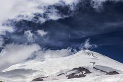 La vue à la neige a couvert le dessus de montagne de ciel bleu sur le fond Photo stock