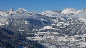 La vue éloignée de Saanen et de neige a couvert des montagnes Photo stock