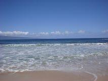 La vue éloignée du bateau à voile en tant que vagues se déplacent le long du rivage Image stock