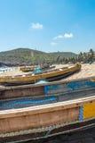 La vue étroite du groupe de bateaux de pêche s'est garée en bord de la mer avec les personnes et la falaise à l'arrière-plan, Vis Photographie stock