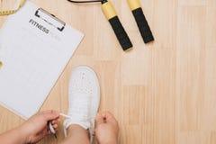 La vue aérienne de la femme remet attacher des chaussures avec des équipements de sport sur le fond en bois images libres de droits