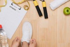 La vue aérienne de la femme remet attacher des chaussures avec les équipements de sport o images stock