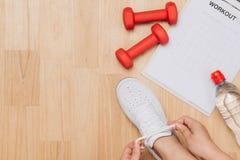 La vue aérienne de la femme remet attacher des chaussures avec les équipements de sport o photo stock
