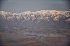 La vue a?rienne de l'avion du Wasatch Front Rocky Mountain Range avec la neige a couvert des cr?tes en hiver comprenant les ville photos stock