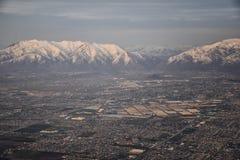 La vue a?rienne de l'avion du Wasatch Front Rocky Mountain Range avec la neige a couvert des cr?tes en hiver comprenant les ville photographie stock libre de droits