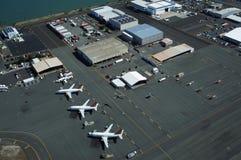 La vue aérienne des avions, des hélicoptères, et des voitures a garé par des bâtiments Photo stock