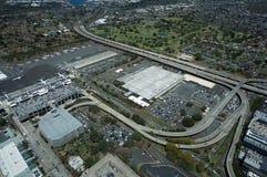La vue aérienne des avions, des hélicoptères, et des voitures a garé par des bâtiments Photographie stock libre de droits