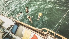 La vue aérienne des jeunes sautant du bateau à voile à la partie se déclenchent Photos stock