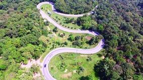 La vue aérienne du bourdon des voitures passent par une route de courbe sur la montagne avec la forêt verte banque de vidéos