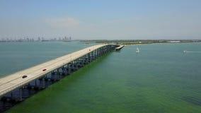 La vue aérienne du bourdon 4k de stupéfaction sur le pont en acier de route énorme de route à travers l'océan bleu calme arrosent clips vidéos