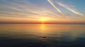 La vue aérienne du lever de soleil d'or au-dessus de l'eau et de l'ondulation de mer ondule