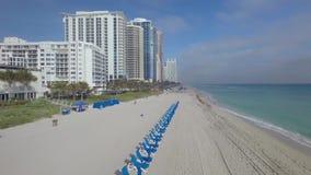 La vue aérienne stupéfiante d'appareil-photo du bourdon 4k sur les chaises de plage bleues de plate-forme sur le sable blanc étay banque de vidéos