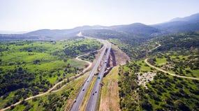 La vue aérienne a tiré voler au-dessus des gisements de collines vertes, présente la route de route et le pont moderne Image libre de droits