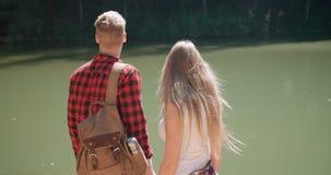La vue arrière d'étreindre des couples se tenant sur un lac étayent dans une forêt Photo stock