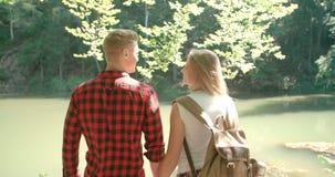 La vue arrière d'étreindre des couples se tenant sur un lac étayent dans une forêt Images stock