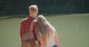 La vue arrière d'étreindre des couples se tenant sur un lac étayent dans une forêt banque de vidéos