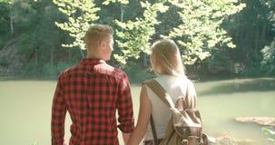 La vue arrière d'étreindre des couples se tenant sur un lac étayent dans une forêt clips vidéos