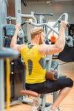 La vue arrière d'un bodybuilder puissant avec fait violence l'exercice au gymnase photos stock