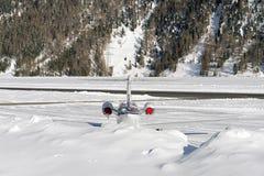 La vue arrière d'un jet privé dans la neige a couvert l'aéroport dans les alpes Suisse en hiver Image stock