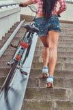 La vue arrière d'une femelle mince sexy a habillé une chemise rose de flanelle et les shorts de denim, monte les escaliers avec u Image libre de droits