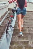 La vue arrière d'une femelle mince sexy a habillé une chemise rose de flanelle et les shorts de denim, monte les escaliers avec u Photographie stock
