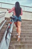 La vue arrière d'une femelle mince sexy a habillé une chemise rose de flanelle et les shorts de denim, monte les escaliers avec u Photo libre de droits