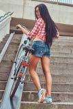 La vue arrière d'une femelle mince sexy a habillé une chemise rose de flanelle et les shorts de denim, monte les escaliers avec u Images stock