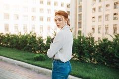 La vue arrière d'une fille rouge de cheveux d'étudiant d'adolescent avec des taches de rousseur marchant sur un chemin à un campu photographie stock