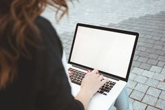La vue arrière de la femme d'affaires est allumée travail sur le clavier d'ordinateur portable dehors à urbain photo stock