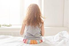 La vue arrière de la jeune femelle bouclée dans des pyjamas se repose du côté du lit, apprécie le soleil de la fenêtre, admire le photo stock