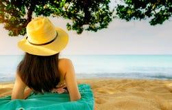 La vue arrière de la jeune femme asiatique heureuse dans le maillot de bain rose et le chapeau de paille détendent et apprécient  image stock